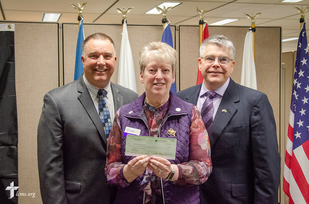 """Christie Steffans, president of the LWML Missouri District, visited the LCMS International Center in St. Louis on Tuesday, April 3, 2018, to present a check for $27,750 to LCMS Ministry to the Armed Forces (MAF). The donation was the mission grant """"Christ for Veterans and Their Families,"""" which Steffans was making on behalf of national LWML. Accepting the grant for MAF were Chaplain Craig Muehler, director, and Chaplain Steven Hokana, assistant director. LCMS Communications/Frank Kohn"""