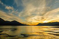 Setting sun over Chugach and Kenai Mountains and the tidal flats of Turnagain Arm in Southcentral Alaska. Summer. Evening.