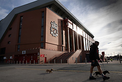 LIVERPOOL, ENGLAND - Tuesday, March 17, 2020: A man walks dogs past a near deserted Anfield, home of Champions-elect Liverpool Football Club, after the suspension of all football due to the Coronavirus (COVID-19) and Liverpool's decision to close it's Boot Room cafe and official stores. (Pic by David Rawcliffe/Propaganda)