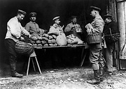 Wilhelm II of German ordered that bread eaten by his soldiers should be served at his own table. Here army officers with baskets are standing round trestle table loaded with loaves and sacks of flour, April 1915.  World War I.