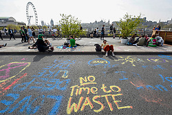 "© Licensed to London News Pictures. 18/04/2019. LONDON, UK.  Graffiti on the road as people on Waterloo Bridge take part in ""London: International Rebellion"", on day four of a protest organised by Extinction Rebellion, demanding that governments take action against climate change.  Marble Arch, Oxford Circus, Piccadilly Circus, Waterloo Bridge and Parliament Square have been blocked by activists in the last three days.  Police have issued a section 14 order requiring protesters to convene at Marble Arch only so that the protest can continue.  Photo credit: Stephen Chung/LNP"