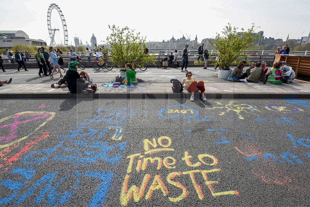 """© Licensed to London News Pictures. 18/04/2019. LONDON, UK.  Graffiti on the road as people on Waterloo Bridge take part in """"London: International Rebellion"""", on day four of a protest organised by Extinction Rebellion, demanding that governments take action against climate change.  Marble Arch, Oxford Circus, Piccadilly Circus, Waterloo Bridge and Parliament Square have been blocked by activists in the last three days.  Police have issued a section 14 order requiring protesters to convene at Marble Arch only so that the protest can continue.  Photo credit: Stephen Chung/LNP"""