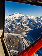 Over Tokositna Glacier, fly towards the huge mountain of Denali, in Denali National Park and Preserve, Alaska, USA. See a vast wilderness of glaciers, icy peaks, and mile deep granite gorges in the Alaska Range. Denali (20,310 feet or 6191 meters, aka Mount McKinley) is the highest mountain peak in North America. Measured from base to peak, it is earth's tallest mountain on land. Mount McKinley is a granitic pluton uplifted by tectonic pressure while erosion has simultaneously stripped away the softer sedimentary rock above and around it.