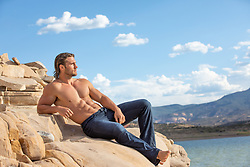 sexy man in jeans and no shirt on a rock by a lake