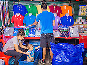 23 AUGUST 2014 - BANGKOK, THAILAND:        A Thai family sets up their clothing stand at a night sidewalk market on Sukhumvit Road near Soi 5 in the Nana section of Bangkok. The Thai military junta, formally called the National Council for Peace and Order (NCPO), has ordered street vendors off of the sidewalks in an effort to bring order to Bangkok's chaotic sidewalks. Vendors have complained that the new regulations are hurting them economically but largely complied with the military orders.  PHOTO BY JACK KURTZ
