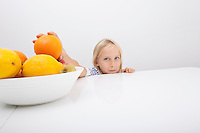 Portrait of little girl holding orange from fruit bowl