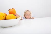 Portrait of little girl holding orange from fruit bowl