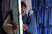 Afghan man and woman in burqa at a burqa shop in Kabul, Afghanistan. 2002