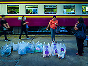 31 MAY 2017 - CHACHOENGSAO, THAILAND:  A passenger buys a premade meal from a vender before boarding a Bangkok bound train at the train station in Chachoengsao, a provincial town about 50 miles and about an hour by train from Bangkok. The train from Chachoengsao to Bangkok takes a little over an hour but traffic on the roads is so bad that the same drive can take two to three hours. Thousands of Thais live outside of Bangkok and commute into the city for work on trains, busses and boats.      PHOTO BY JACK KURTZ