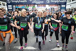 © Licensed to London News Pictures . 19/05/2019. Manchester, UK. Mother of Saffie Roussos , LISA ROUSSOS completes the race with supporters from her charity 22 MCR . Participants at the finish line of the 10k run in the Great Manchester Run in Manchester City Centre . Photo credit : Joel Goodman/LNP
