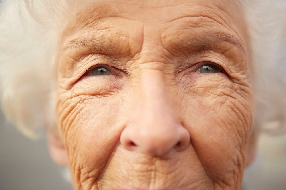 Close up portrait photograph of senior citizen woman thinking about life