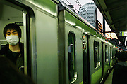 The open doors of a train in a Tokyo subway station reveal a young man wearing a filtering mask for air pollution
