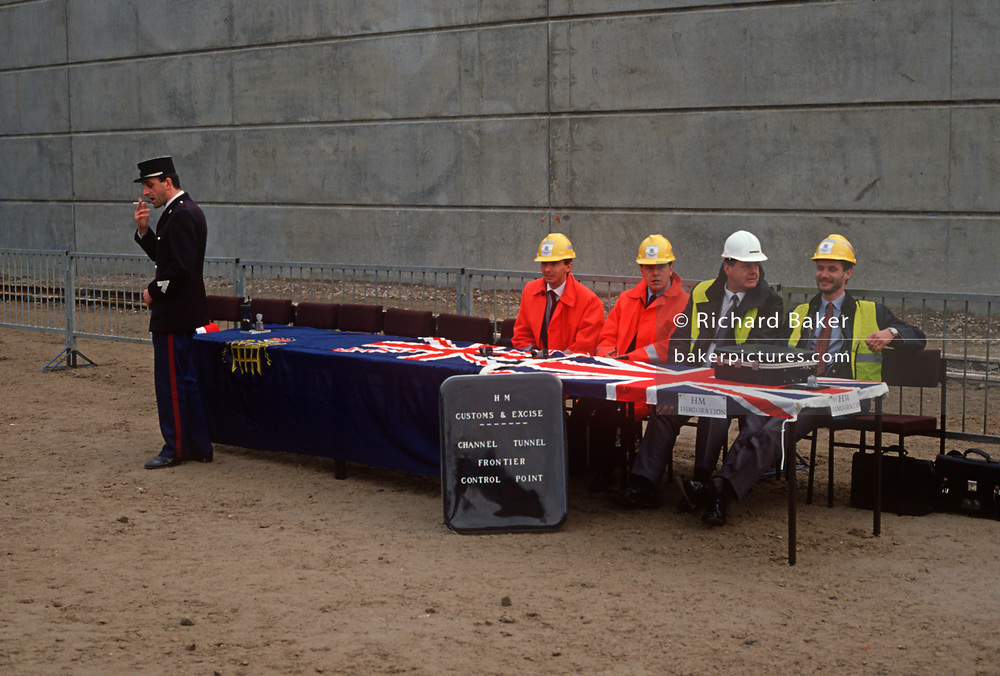 1990s British customs and immigration officials and a French Gendarme await the arrival of the first people to have crossed from France to the British mainland on the occasion of the Channel Tunnel bores breaking through, on 1st December 1990, in Folkestone, Kent England.