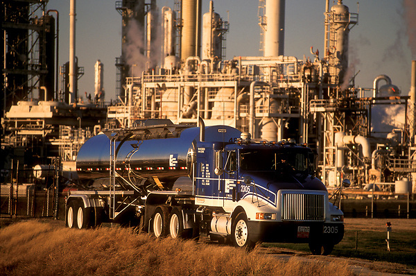 Large blue liquid transport truck parked in front of a refinery