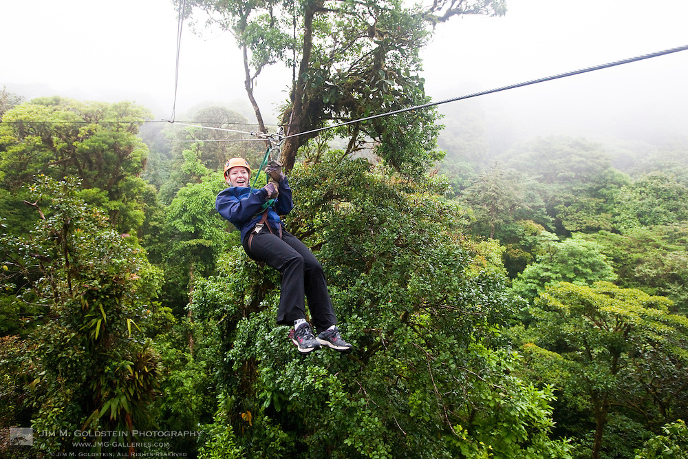 A young woman comes in from a long zip line ride in the Monteverde Cloud Forest Reserve in Selvatura Adventure Park, Costa Rica
