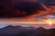 The sun rises over the Pacific Ocean, lighting up the sky above the crater in Haleakala National Park, Maui, Hawaii.