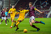 Steve Lawson (#33) of Livingston FC and Christophe Berra (#6) of Heart of Midlothian FC tussle for the ball during the Ladbrokes Scottish Premiership match between Heart of Midlothian FC and Livingston FC at Tynecastle Park, Edinburgh, Scotland on 4 December 2019.