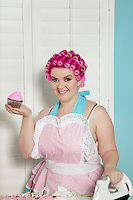 Portrait of happy young woman holding cupcake while ironing
