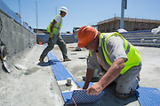 Richard Lamb, foreground, lays down lane marker tiles in the warming pool at Milpitas High School in Milpitas, California, on July 18, 2014. (Stan Olszewski/SOSKIphoto)