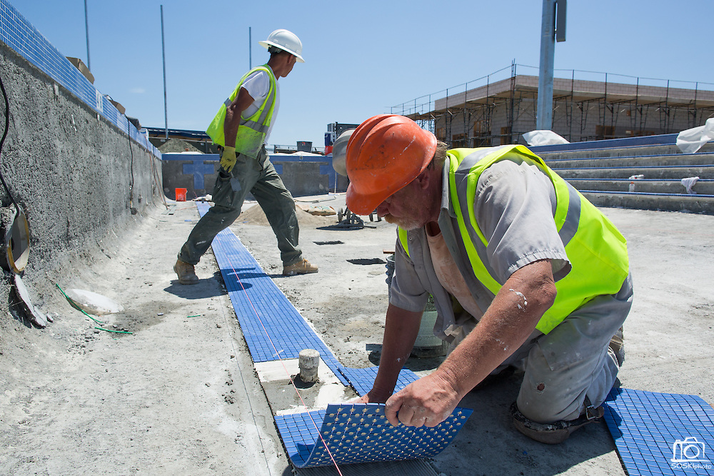 Richard Lamb, foreground, lays down lane marker tiles in the warming pool at Milpitas High School in Milpitas, California, on July 18, 2014. (Stan Olszewski/SOSKIphoto)