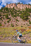 Cyclist passing the Rio Grande Palisades on Highway 149, Rio Grande National Forest, Colorado