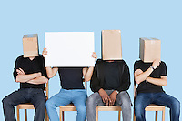 Man holding blank cardboard with male friends faces covered with boxes over blue background