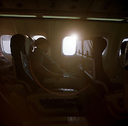 As bright sunlight glares through the window of an airliner, a sleeping male passenger reclines in his seat on a transatlantic flight.