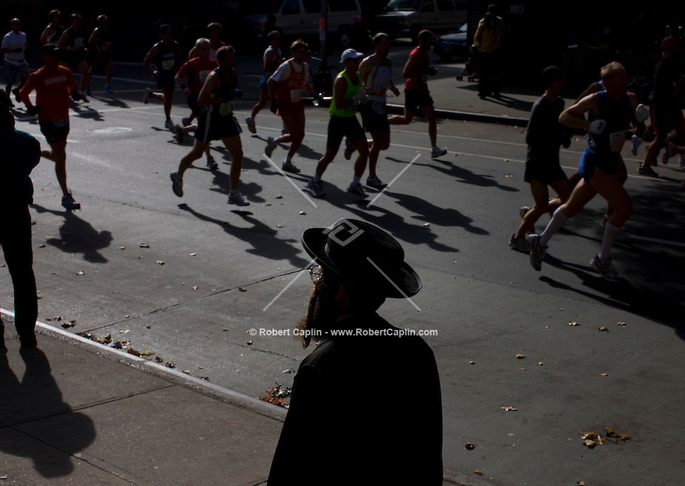 Hasidic Jews are seen silhouetted as the first runners pass mile 10 on Bedford Ave. in South Williamsburg, Brooklyn during the ING New York City Marathon, Sunday, Nov. 2, 2008. Robert Caplin For The New York Times