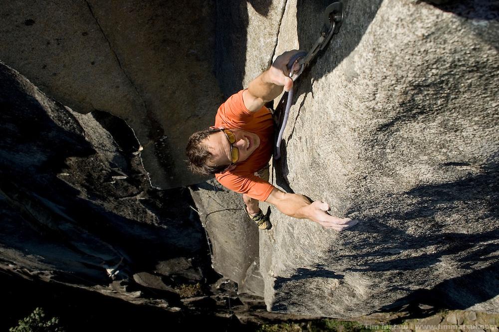 A man climbing steep granite rock in Index, Washington, near Seattle.