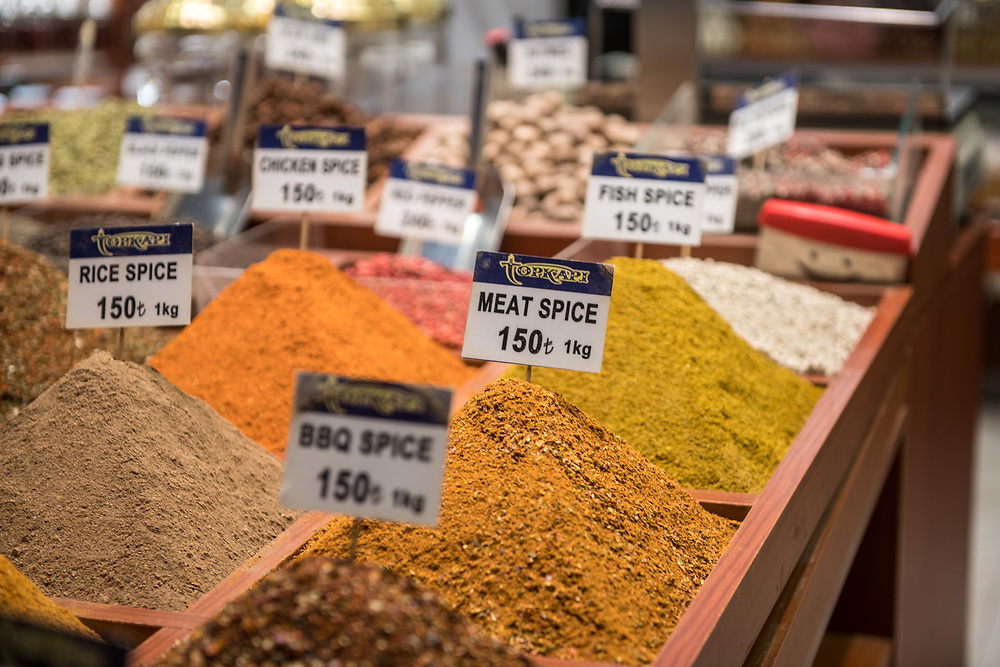 Tidy piles of fresh spices organized in wooden tray of market stall, Istanbul Spice bazaar in Turkey