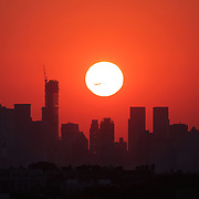 The sun sets behind the Manhattan skyline as a plane passes through the sun viewed from Arthur Ashe  Stadium during the US Open Tennis Tournament, Flushing, New York. USA. 31st August 2012. Photo Tim Clayton