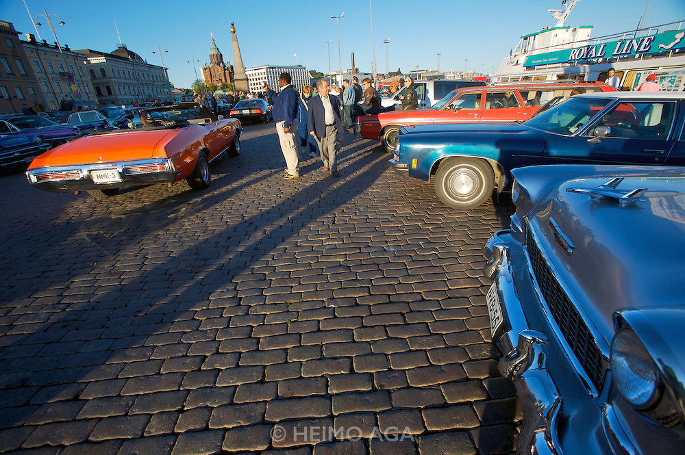 During summer from June to Septemper, every first Friday of the month is Vintage Car Cruising Night. Hundreds of classic American cars cruise around downtown Helsinki and meet at special places to have a good time, here at Kauppatori (Market Square), Uspenski orthodox cathedral in background. 1955 Chevy 210 four door sedan (foreground r.)