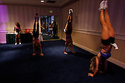 "Baltimore Ravens cheerleader hopefuls perform hand stands while warming up before taking to the stage during an event called ""Making the Cut"" to select the 2011 Baltimore Ravens cheerleaders in Baltimore, Maryland, March 26, 2011.  Each March hopeful men and women travel to Baltimore, Maryland to tryout for the Baltimore Ravens Cheerleaders. Competition is especially tough for the only co-ed cheerleading team in the NFL, where even veterans have to tryout to protect their spot on the squad. During the first two intense days of tryouts the field is reduced from hundreds to just 100 competing for 60 spots. The final day of tryouts, called Making the Cut, is held in a hotel ballroom during a televised event open to the public."