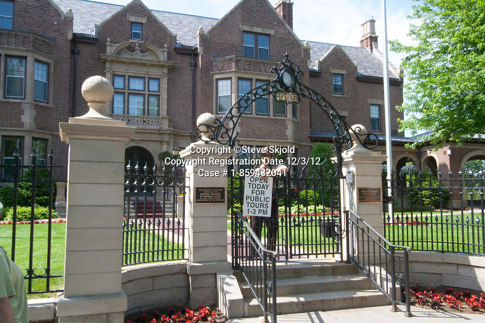 Hiway patrol officer placing visiting hours sign on front gate of Governor's Residence Mansion. St Paul Minnesota MN USA
