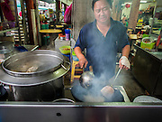 07 OCTOBER 2014 - GEORGE TOWN, PENANG, MALAYSIA: A food vendor fries noodles in a tea shop in George Town (also Georgetown), the capital of the state of Penang in Malaysia. Named after Britain's King George III, George Town is located on the north-east corner of Penang Island. The inner city has a population of 720,202 and the metropolitan area known as George Town Conurbation which consists of Penang Island, Seberang Prai, Kulim and Sungai Petani has a combined population of 2,292,394, making it the second largest metropolitan area in Malaysia. The inner city of George Town is a UNESCO World Heritage Site and one of the most popular international tourist destinations in Malaysia.         PHOTO BY JACK KURTZ