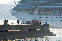 Large Cruise ship and people watching ship back into her berth from the pier at Ogden point.  Victoria, British Columbia, Canada.