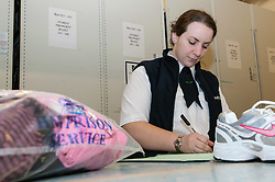 Prison officer searching packages for prisoners, HMP Bronzefield, women's prison in Surrey