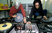 Two men with decks and other music equipment, one wearing a silver mask