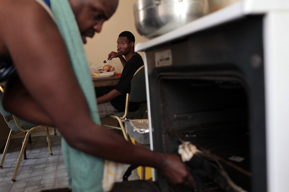 William Horne, left, cooks lunch watched by Shelvy Clark, background, at his home in Baltimore, MD on August 8, 2010. William Horne lost his home in a rent-back scheme and is currently suing the company. For ProPublica on the Baltimore foreclosure story. .Photographer: Melanie Burford for ProPublica.