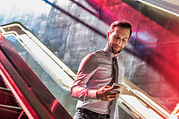Portrait of young attractive businessman using smartphone while walking downstairs