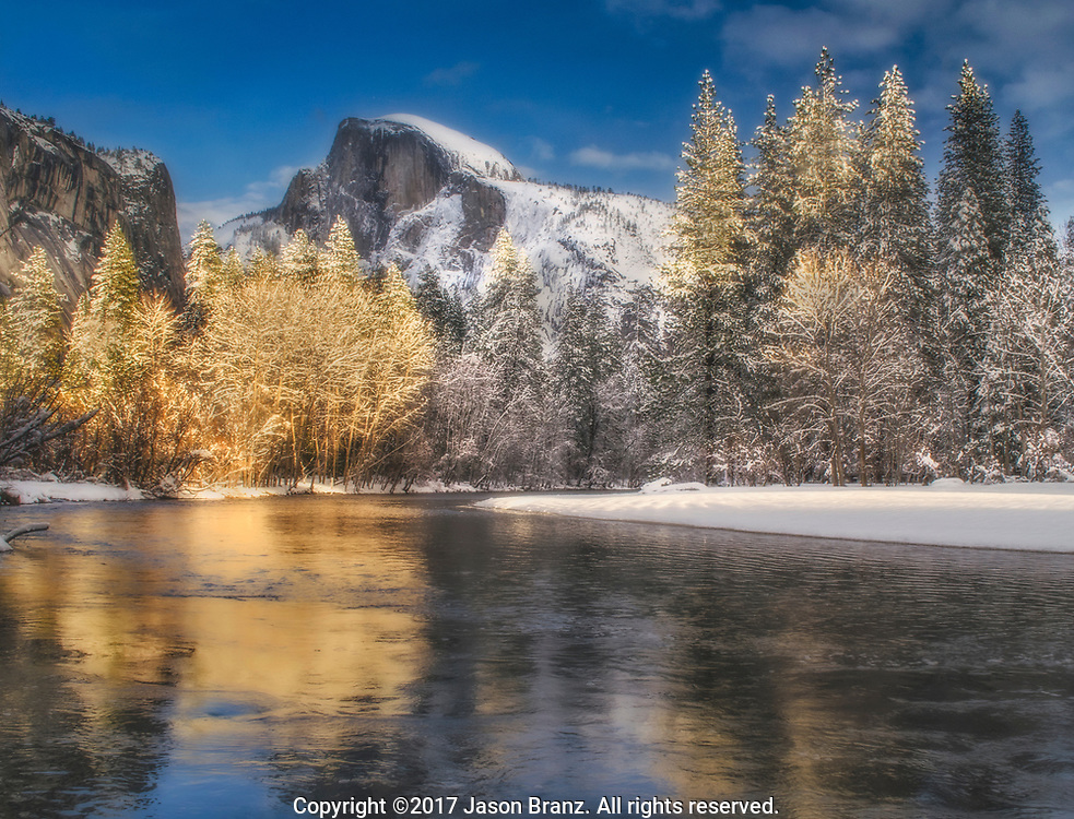 Late afternoon light on Half Dome and snowy trees along the Merced River, Yosemite National Park, California.