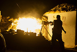 © Licensed to London News Pictures. 01/09/2015. Bashiqa, Iraq. A Kurdish peshmerga fighter fires a DShK heavy machine gun at ISIS vehicles moving near his unit's defensive position on Bashiqa Mountain, Iraq.<br /> <br /> Bashiqa Mountain, towering over the town of the same name, is now a heavily fortified front line. Kurdish peshmerga, having withdrawn to the mountain after the August 2014 ISIS offensive, now watch over Islamic State held territory from their sandbagged high-ground positions. Regular exchanges of fire take place between the Kurds and the Islamic militants with the occupied Iraqi city of Mosul forming the backdrop.<br /> <br /> The town of Bashiqa, a formerly mixed town that had a population of Yazidi, Kurd, Arab and Shabak, now lies empty apart from insurgents. Along with several other urban sprawls the town forms one of the gateways to Iraq's second largest city that will need to be dealt with should the Kurds be called to advance on Mosul. Photo credit: Matt Cetti-Roberts/LNP