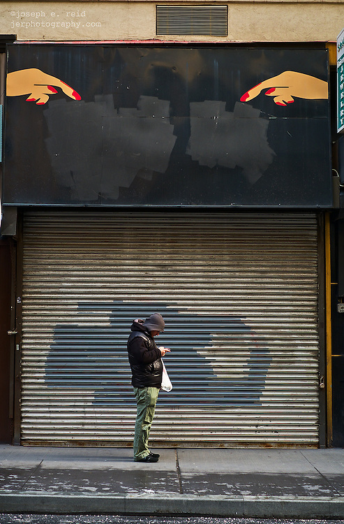 Man using smartphone under illustration of pointing fingers on closed shop facade