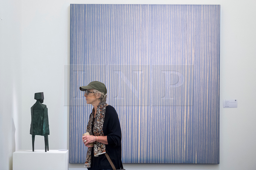 """© Licensed to London News Pictures. 16/11/2018. LONDON, UK. A visitor views """"Conjunction XII"""", 1970, by Lynne Chadwick (Est. GBP50,000-80,000) in front of """"Repetition (Grey/Violet)"""", 1995, by Callum Innes (Est. GBP12,000-18,000).  Preview of Sotheby's autumn sale of Modern & Post War British art.  Works from the British art scene of the past century will be offered for sale on 20 and 21 November 2018 at Sotheby's in London.  Photo credit: Stephen Chung/LNP"""