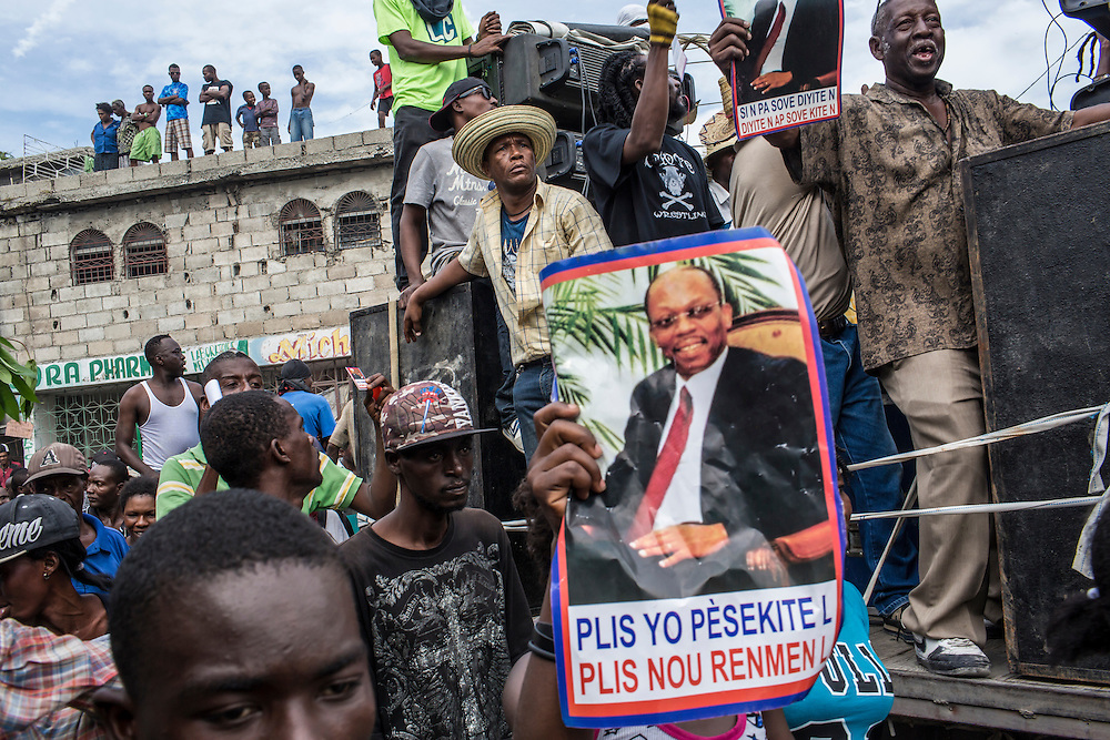 People hold a picture of former Haitian president Jean-Bertrand Aristide during an anti-government protest on Tuesday, December 16, 2014 in Port-au-Prince, Haiti. President Michel Martelly was elected in 2010 with great hope for reforms, but in the wake of slow recovery and parliamentary elections that are three years overdue, his popularity has suffered tremendously, forcing Prime Minister Laurent Lamothe to resign.