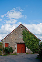 Chateauneuf-en-Auxois. Stone barn partly covered by a creeper.  The red wooden door makes the building even more attractive.