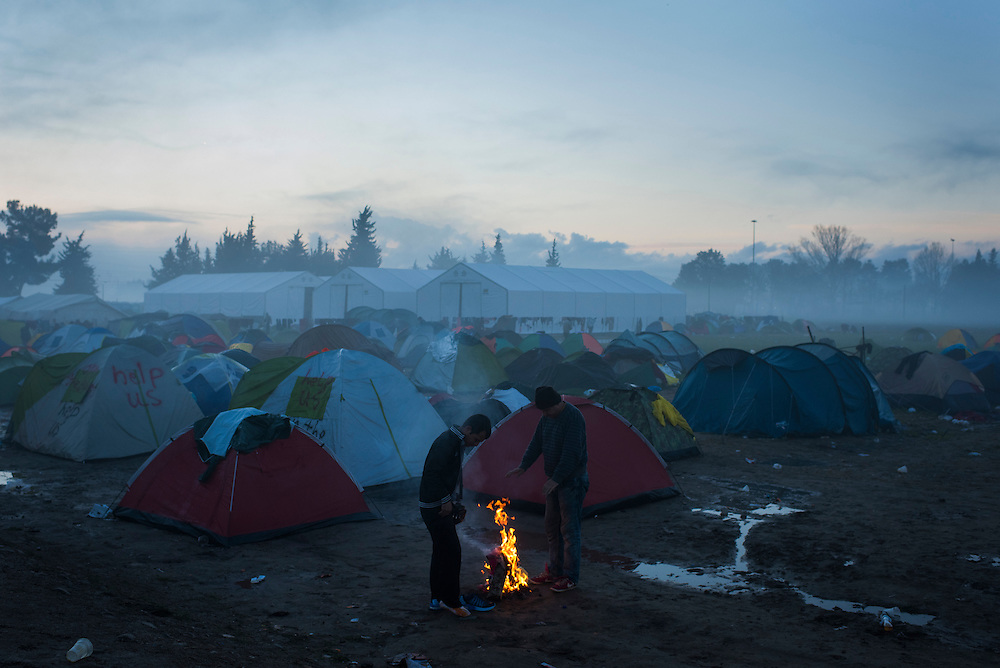 Refugees warm themselves by a fire at dawn near the Macedonian (FYROM) border on March 8, 2016 in Idomeni, Greece.