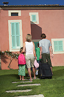 Family with three children (6-11) entering house with luggage back view
