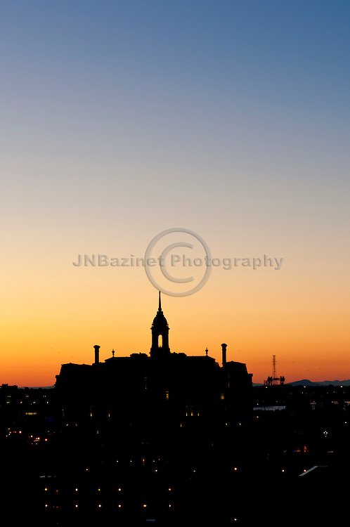 With gulls flying overhead, the sunrises above City Hall in Montreal, QC Canada