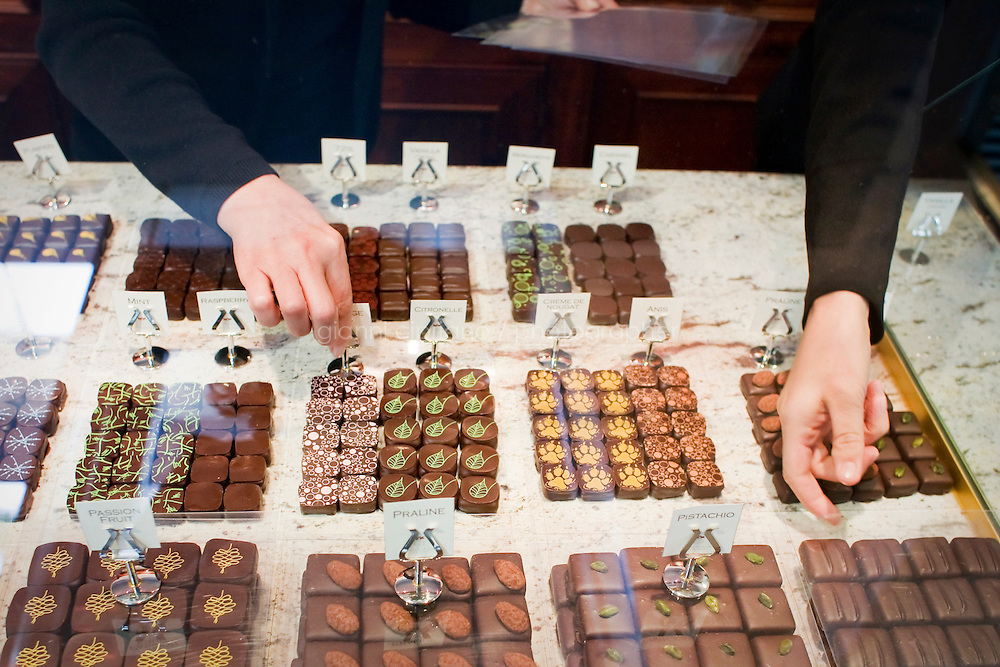 24 October, 2008. New York, NY. Owner Namhee Girerd Kim, 53, picks an assortment of bon bons and fills a box at the boutique &quot;L'atelier du chocolat&quot;. The chocolates are made by her husband, Eric Girerd. The stand at the entrance of the shop displays an assortment of chocolate bon bons, including flavors such as herbs. salt, fruit, spices, and classic chocolates.<br /> <br /> &copy;2008 Gianni Cipriano for The New York Times<br /> cell. +1 646 465 2168 (USA)<br /> cell. +1 328 567 7923 (Italy)<br /> gianni@giannicipriano.com<br /> www.giannicipriano.com